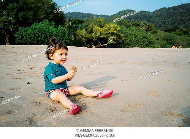 Thailand, Koh Lanta, smiling baby girl wearing UV protection shirt sitting on the beach playing with sand