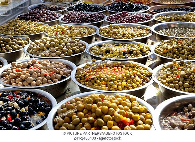 Variety of black and green olives in bowls on the market