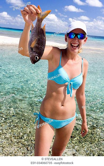 Girl in a bikini holding a tropical fish on a beach in Aitutaki in The Cook Islands in the South Pacific