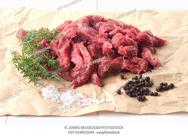 beef cut into small stripes with thyme, coarse salt and pepper on brown kitchen paper