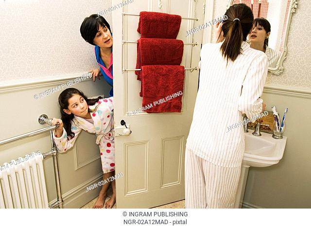 Mid adult woman with her daughter peeking at teenage girl standing in front of a mirror