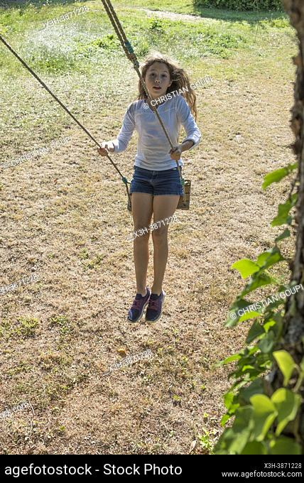 Young girl in jeans shorts and white tunic on a swing in motion, France