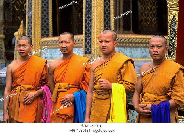 Monks with rice bowls ready to accept tithes from locals in Bangkok Thailand - 01/01/2014