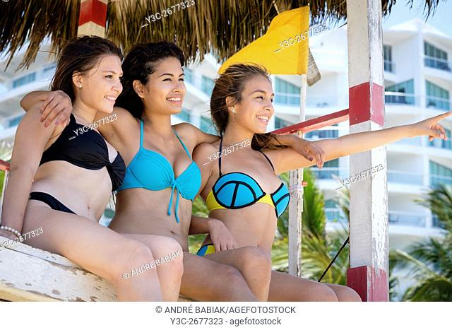 Group of 3 female teenagers in bikinis having fun on life guard watch tower at a beach in Mexico