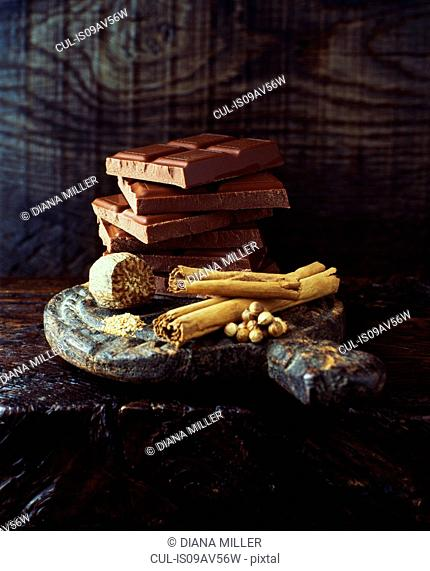 Cinnamon stick, nutmeg and broken chocolate bars stacked on wooden cutting board