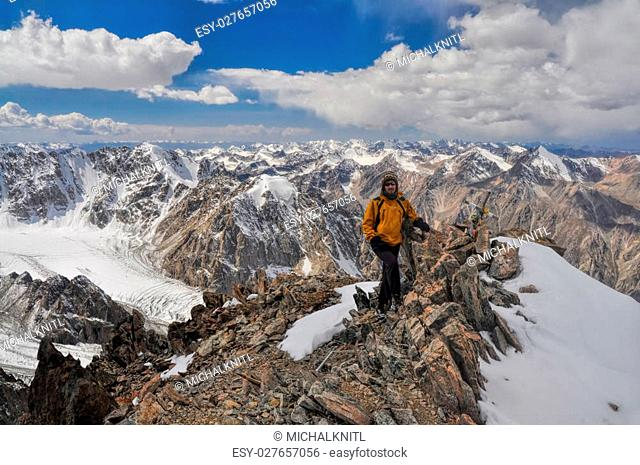 Adventurous young hiker on mountain summit in scenic Tian Shan range in Kyrgyzstan, Ala Archa national park