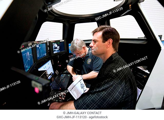 NASA astronauts Greg Chamitoff (foreground), STS-134 mission specialist; and Greg H. Johnson, pilot, participate in an exercise in the systems engineering...