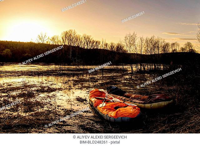 Inflatable rafts on shore of river at sunset