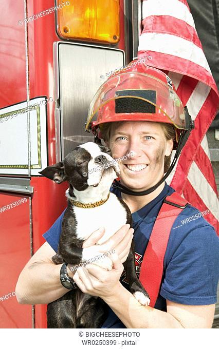 Female firefighter holding Boston Terrier