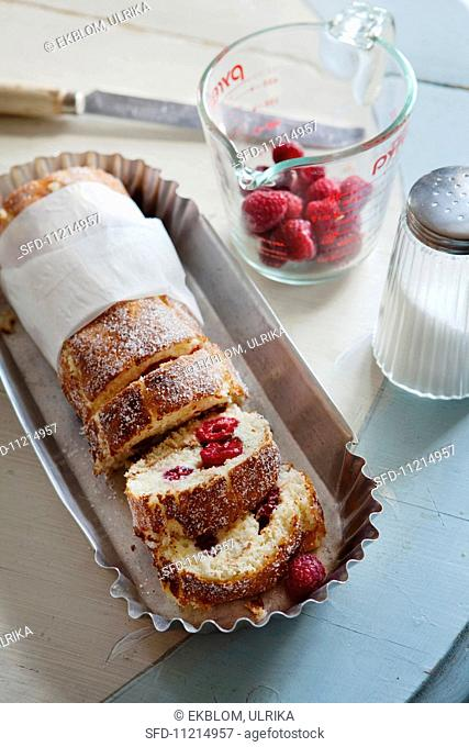 Lime Swiss roll with a raspberry and mascarpone filling, partially sliced
