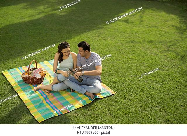 Man pouring wine for woman on picnic blanket