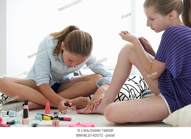 Caucasian girls painting their nails