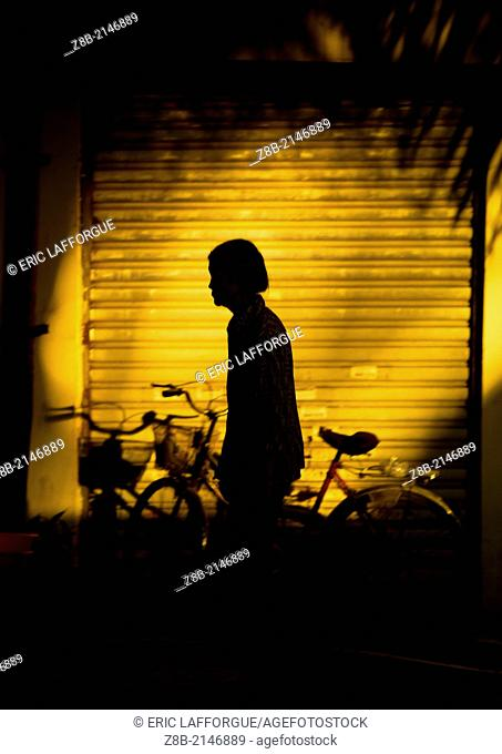 Silhouette Of A Woman In The Street, Menglun, Yunnan Province, China