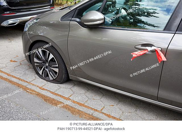 10 July 2019, Hamburg: Peugeot stands with a flat tire and with a police barrier tape attached to the door handle on the parking strip of the street Weg at the...