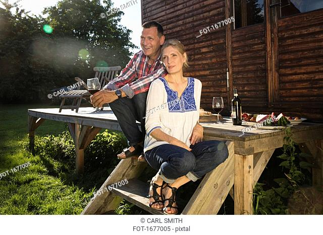 Mature couple enjoying wine while sitting outside farmhouse