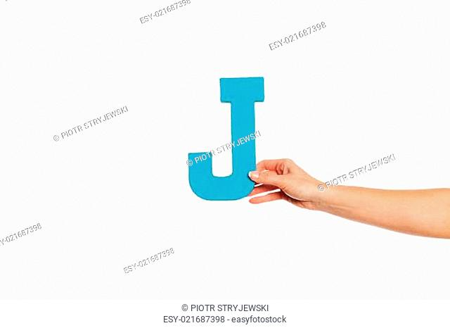 hand holding up the letter J from the right