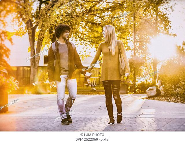 Boyfriend and girlfriend walking and holding hands on the university campus at sunset; Edmonton, Alberta, Canada