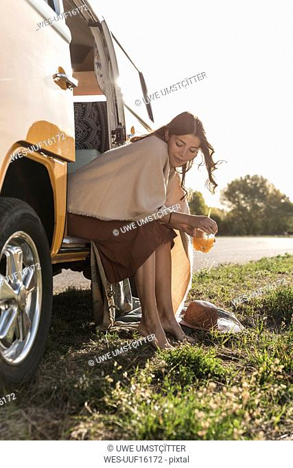 Pretty woman on a road trip with her camper, taking a break, drinking juice