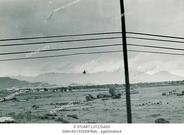 A United States Marine Corps helicopter flies low over a rural landscape of rice paddies, with power lines in the foreground, during the Vietnam War, 1968