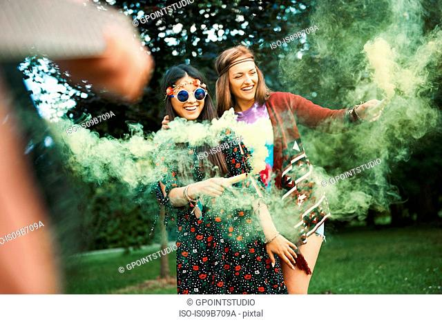 Young boho women dancing with green smoke flare at festival