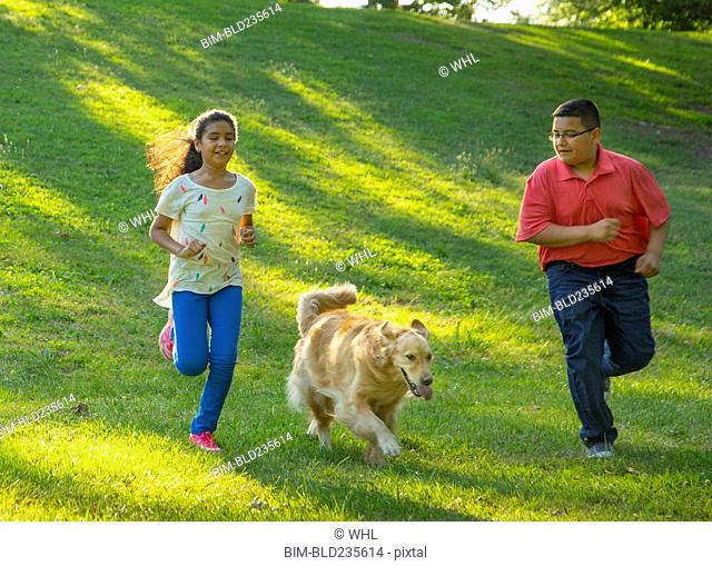 Hispanic brother and sister running with dog on hill