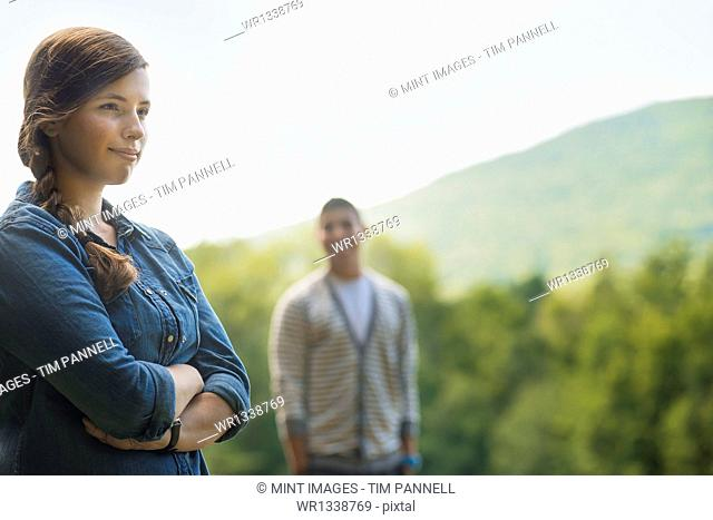 A man and woman standing in evening light outdoors at a distance, a tranquil scene
