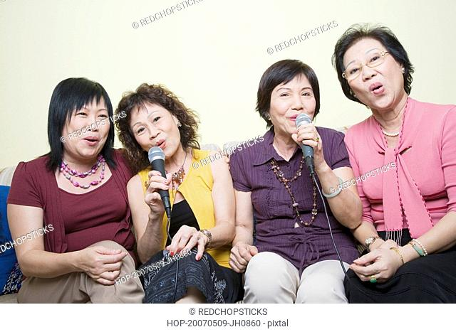 Three senior women and a mature woman singing in front of microphones