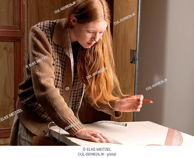 Young female fashion designer measuring dressmaker's pattern