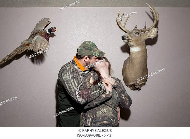 Mid adult couple kissing with animal taxidermy on walls