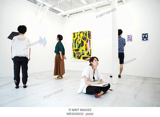Woman with black hair sitting on floor in art gallery with pen and paper, looking at modern painting, three people standing in front of artworks
