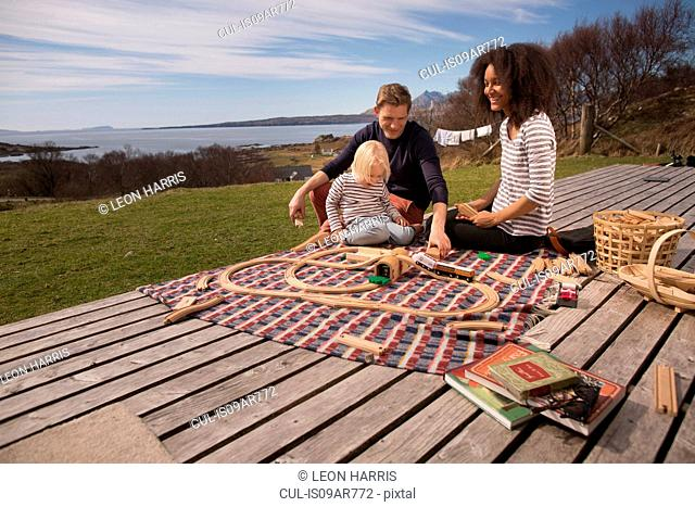 Boy and parents playing with toy train on wooden decking