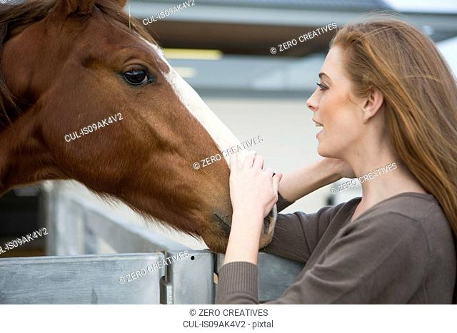 Female stablehand petting chestnut horse in stables