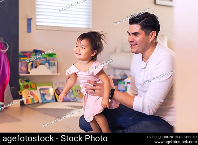 Baby sitting on the floor in play room holding baby daughter