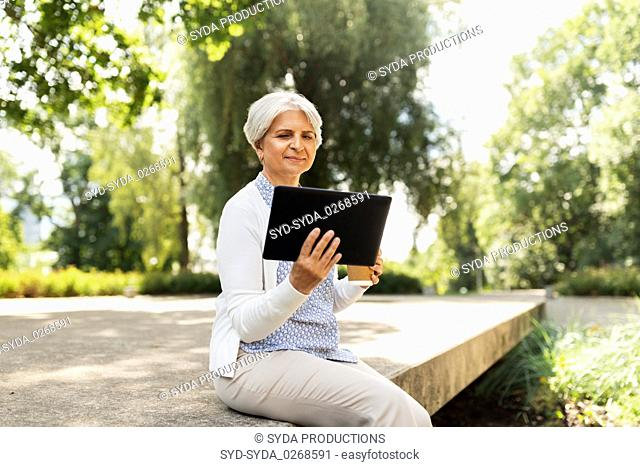old woman with tablet pc and coffee at summer park