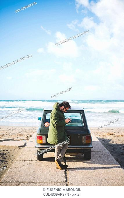 Man with vintage car parked on beach reading smartphone texts, Sorso, Sassari, Sardinia, Italy