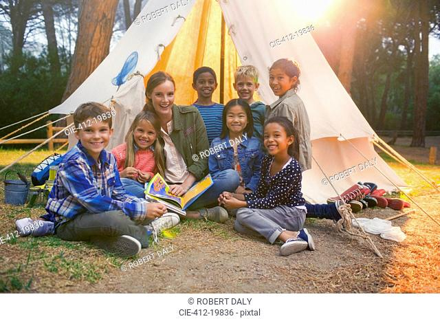 Students and teacher smiling at campsite