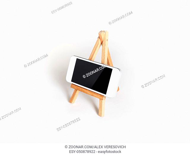 Photo of mobile phone with blank screen on wood holder at white paper background