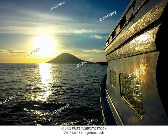 Sunset over volcano Manado Tua and reflection at boat at Manado, Sulawesi, Indonesia