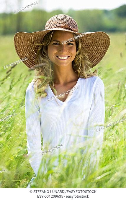 Beautiful woman in field with straw hat