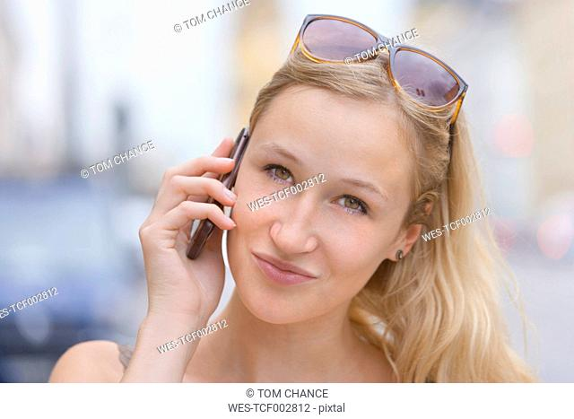 Germany, Bavaria, Munich, Young woman talking on phone in front of Bavarian State Library at Ludwigstrasse