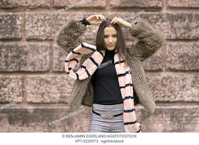 playful woman with scarf in front of brick wall, in Munich, Germany