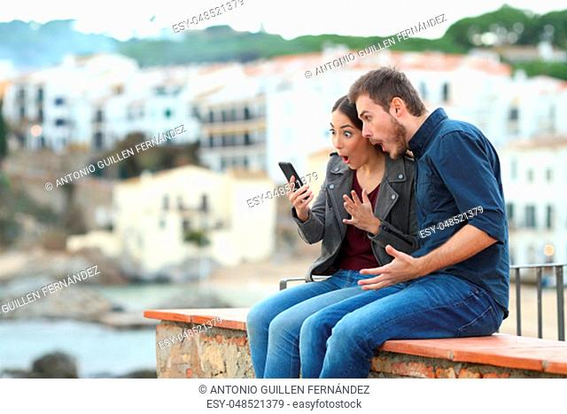 Surprised couple on vacation reading news on a smart phone sitting on a ledge on vacation in a coast town