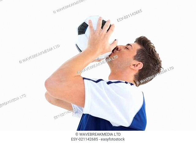Football player in blue kissing the ball
