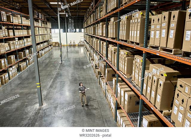 A view from above looking down on a warehouse worker checking inventory of boxes on racks in a distribution warehouse