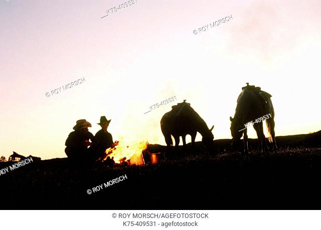 Couple of ranchers at campfire with horses