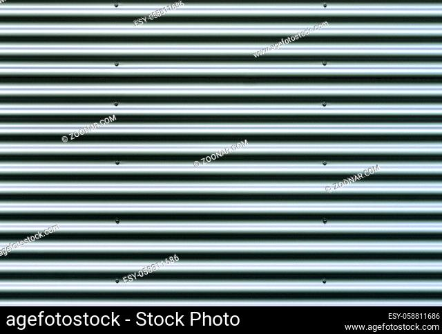Closeup stainless steel corrugated sheet. Ridged reinforced metal surface for protection. Metallic background texture