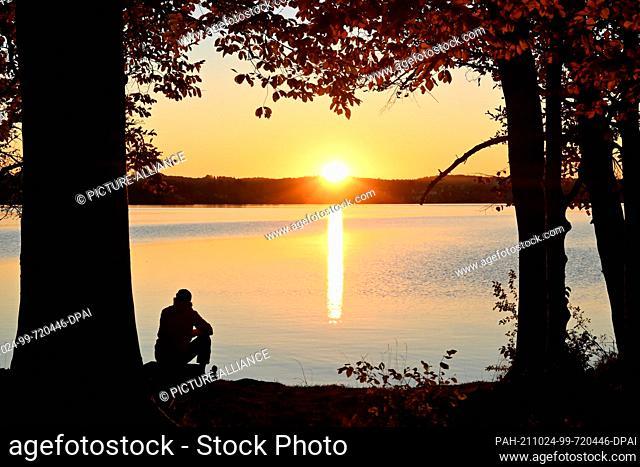 24 October 2021, Bavaria, Sankt Heinrich: A man sits on the shore of Lake Starnberg in Sankt Heinrich in the municipality of Münsing (Bad Tölz-Wolfratshausen...