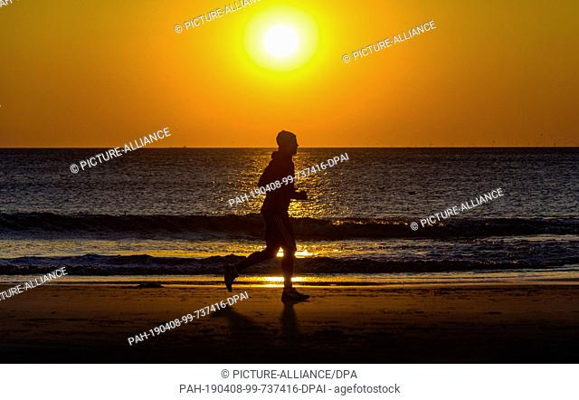 08 April 2019, Schleswig-Holstein, Westerland/Sylt: A jogger walks along a beach of Sylt before a setting sun and cloudless sky