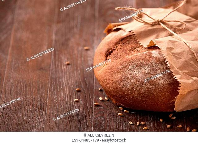 Loaf of rye bread in paper bag on wooden table. Bakery background. Decorative rope. Flour. Brown background. Tasty and appetizing