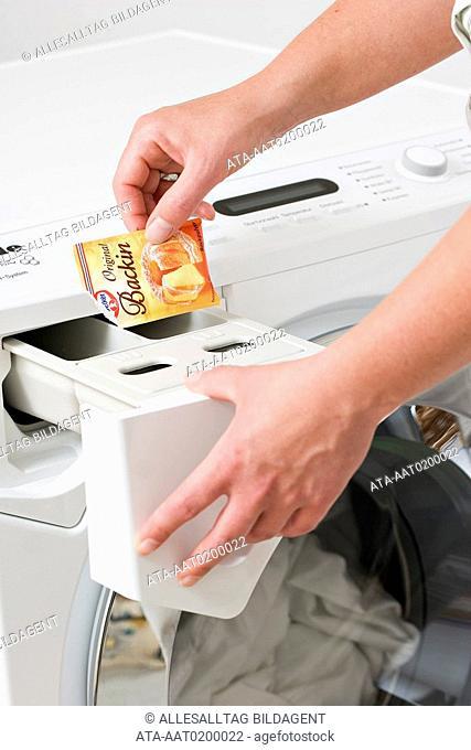 Woman filling sodium bicarbonate into the washing machine